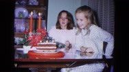 1967: girl blowing out candles on birthday cake. NEVADA Stock Footage