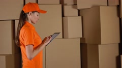 Female warehouse worker in orange uniform counting boxes and using her tablet Stock Footage