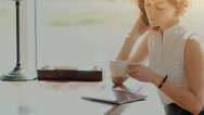 A woman in a cafe , drinking coffee and working on the tablet Stock Footage