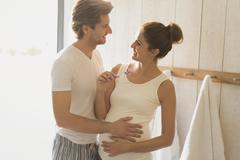 Pregnant couple brushing teeth in bathroom Kuvituskuvat