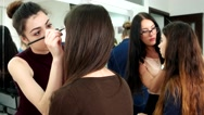 Girl makeup artists do make-up to clients in the salon, evening make-up to Stock Footage