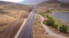 Aerial shot as vehicles drive through a construction zone Stock Footage