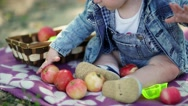 Basket with apples close. Joyful child in nature. Toddler in denim suit and a Stock Footage