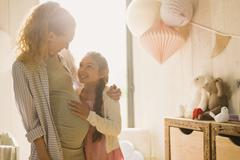 Pregnant mother and daughter in sunny nursery Stock Photos