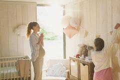 Pregnant mother and daughter decorating sunny nursery Stock Photos