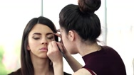 Makeup artist deals eyeshadow cosmetics brush, makeup on face and eyes in the Stock Footage