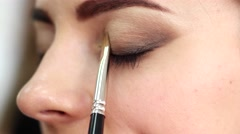Makeup for eyes close up, applying eye shadow brush, girl paints her eyes and Stock Footage