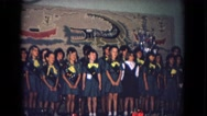 1967: a group of young girls on stage dressed in what appears to be girl scout Stock Footage