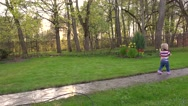 Child girl walk on wet path after rain in summer garden Stock Footage
