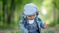 A cute baby. Little boy with apple. Toddler in denim suit and a cap Stock Footage