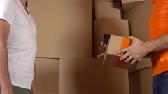 Store assistant in orange uniform giving a box to a customer. Cartons background Stock Footage