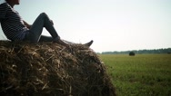 Young stylish girl in a striped t-shirt sitting on a haystack Stock Footage