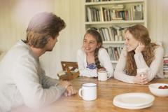 Family drinking tea and talking at dining table Stock Photos
