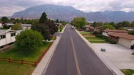 Aerial shot flying above road in mountain city suburb Stock Footage