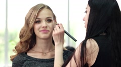 The girl with a brush is applied tone cream makeup, make-up artist works with Stock Footage