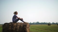 Girl in the countryside. Pretty girl is sitting on haystacks Stock Footage