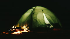 The tent in which the light shines near the fire burning. Romance and relaxation Stock Footage