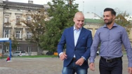 Two businessman are walk while talking. City background Stock Footage