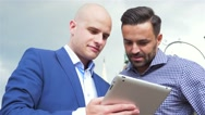 Two businessman are standing and using tablet pc. City background Stock Footage