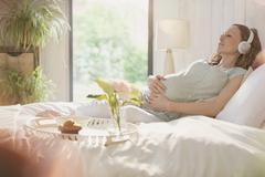 Serene pregnant woman listening to music with headphones on bed Stock Photos
