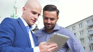 Two businessman are standing and talking while using tablet pc. Stock Footage