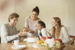 Woman serving cake to family at dining table Stock Photos