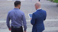 Two young businessmen are walking while using tablet pc. City background Stock Footage