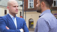 Two young businessmen are having a serious conversation. City background Stock Footage