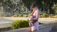 Young mother with baby in sling using smartphone Stock Footage