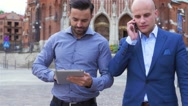 Two young businessmen are walking while using tablet pc and mobile phone Stock Footage