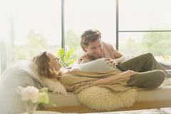 Affectionate pregnant couple laying touching stomach Stock Photos