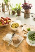 Pasta, fruit, bread, butter and asparagus on dining table Stock Photos