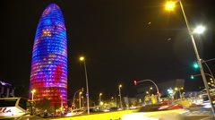 Many cars rushing by illuminated Torre Agbar, hectic night city life, time-lapse Stock Footage