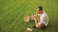 Guy having lunch on meadow. man eating a sandwich on the lawn and drinks juice. Stock Footage