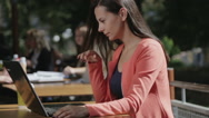 Beautiful woman typing on a laptop computer outdoors. Stock Footage