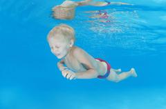 Boy swim under water in the pool Stock Photos