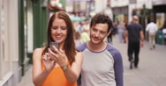 4k, A young woman showing her boyfriend something on a cellphone. Stock Footage