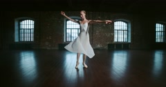 Beautiful ballerina in white dress performs the elements of dance in the loft Stock Footage