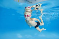 5 years boy in a swimming goggles learning to swim underwater in the pool Kuvituskuvat
