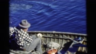 1967: two men on a small metal motor boat fishing in the beautiful blue water Stock Footage