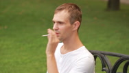 Man smoking thin cigarette at the park Stock Footage