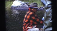 1967: old man in a plaid shirt and hat fishing while on a boat showing catch Stock Footage