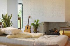 Guitar leaning near fireplace behind chaise in living room Stock Photos