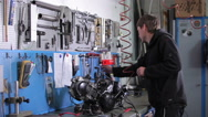 Mechanic takes t-handle screwdriver from pegboard Stock Footage