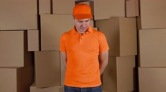 Courier in orange uniform delivering damaged parcel to customer. Brown cartons Stock Footage