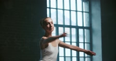 Beautiful ballerina in white dress performs pirouettes in the Studio, slow Stock Footage