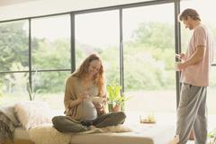Pregnant couple eating and drinking coffee in living room Stock Photos