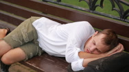 Girl wakes up the sleeping man on the bench. man wakes up from sleep Stock Footage