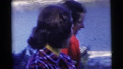 1967: couple women at lake are captured candidly while talking and flash Stock Footage