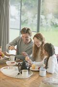 Family eating cupcakes and fruit at dining table Stock Photos